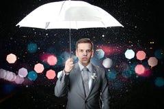 经典衣服的人与在一刹那光和雨下落的白色伞 免版税图库摄影
