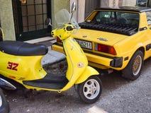 经典黄色比雅久滑行车和菲亚特X19 免版税库存图片