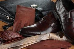 经典黑鞋子、领带、手套和公文包在木木条地板 库存图片