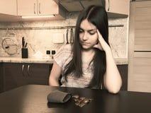 经济的概念,有长的黑发的一名年轻失望的妇女,在一个老空的钱包旁边坐与 库存照片