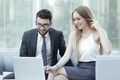 经理和客户关于膝上型计算机的浏览信息 库存图片
