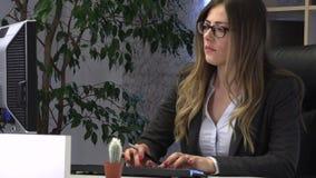 经理在计算机写并且检查文献在桌上 影视素材