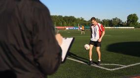 经理检查一个足球运动员,调动 股票录像