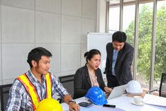 经理检查工程师队的工作 工程师和技术员计划  工程师和建筑师计划 免版税库存照片