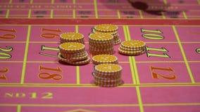经销商工作,位于打赌,在赌博娱乐场收集轮盘赌的芯片 股票录像