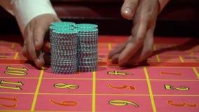 经销商工作,位于打赌,在赌博娱乐场收集轮盘赌的芯片 股票视频