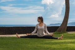 绑腿和长袍的美丽的女孩在巴厘岛印度尼西亚做瑜伽实践,在海洋海滩的凝思 免版税库存图片