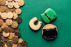 结冰曲奇饼和金黄硬币在绿色, st patricks顶视图  图库摄影