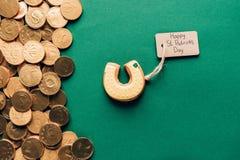 结冰曲奇饼顶视图在马掌和金黄硬币, st patricks形状的在绿色的 免版税库存照片
