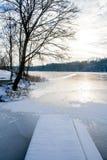 结冰的湖在冬天,当码头、木小船和树盖由雪 库存照片