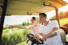 结合乘坐一辆白色高尔夫车在高尔夫球场 库存照片