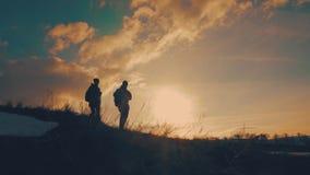 结合互相帮助的远足现出轮廓在山 远足配合的夫妇,互相帮助,信任协助,日落 影视素材
