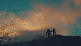 结合互相帮助的远足现出轮廓在山 远足配合的夫妇,互相帮助,信任协助,日落 股票视频