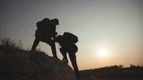 结合互相帮助的远足现出轮廓在山 远足配合的夫妇,互相帮助,信任协助,日落 股票录像