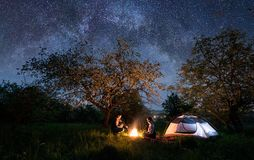 结合充分坐在营火的游人在帐篷在树下和夜空星和银河附近 夜野营 库存照片