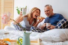 结合吃早餐在吃美味的新月形面包的床 库存图片