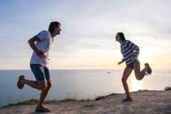 结合在一座山的乐趣消遣有海边视图 男人和妇女一起跳舞在日落侧视图 免版税库存照片
