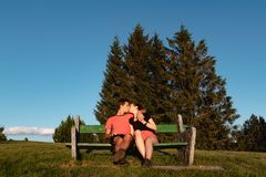 结合在坐在山的长凳和亲吻在远足以后的爱 免版税库存图片