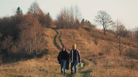 结合在握手的爱远足户外 徒步旅行者人和妇女迁徙的走与在足迹的背包在日落 股票录像