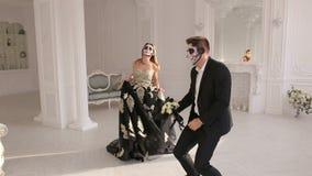 结合在服装,并且构成为万圣节,他们在一个明亮的绝尘室跳舞 股票录像