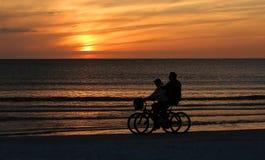 结合在海滩的骑马自行车在日落 库存图片