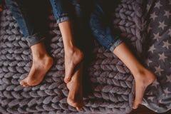 结合在衣裳裤子的人和女孩蓝色在床上 免版税图库摄影