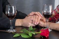 结合在餐馆桌上的手与两杯红酒和玫瑰 库存图片