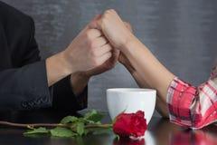 结合在餐馆桌上的手与白色杯子和玫瑰花 免版税库存图片