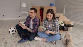 结合坐在他们新的公寓的地板在箱子中并且计数金钱 股票录像