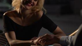 结合坐在桌上在大阳台,给她的手的女性男性,挥动 影视素材