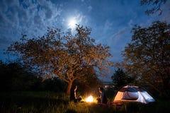 结合坐在营火的游人在帐篷在树下和与月亮的夜空附近 夜野营 免版税库存图片