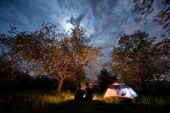 结合坐在营火的游人在帐篷在树下和与月亮的夜空附近 夜野营 免版税图库摄影
