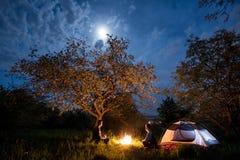 结合坐在营火的游人在帐篷在树下和与月亮的夜空附近 夜野营 免版税库存照片