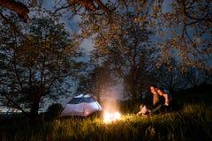 结合坐在营火的游人在帐篷附近,拥抱在树和夜空下 夜野营 免版税库存图片