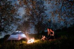 结合坐在营火的游人在帐篷附近,拥抱在树和夜空下 夜野营 免版税库存照片