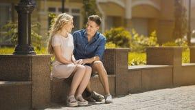 结合坐长凳,人赞赏的白肤金发的女孩在第一个日期,浪漫心情 免版税库存照片