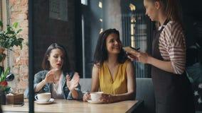 结合女孩谈话与做命令微笑的聊天的咖啡馆的女服务员 股票视频