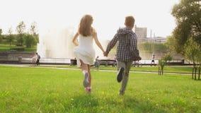 结合手和赛跑的无忧无虑的孩子一体在草在夏天公园 股票录像