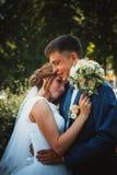 结合拥抱和亲吻在自然公园背景的新郎和新娘 免版税图库摄影