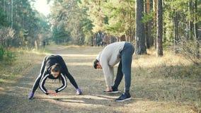 结合朋友男性,并且女性在晴朗的秋天天做着户外弯曲今后在准备期间的体育 健康 股票录像