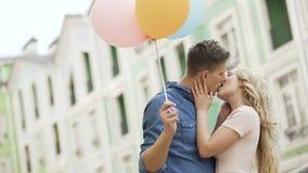结合步行沿着向下街道,停止对亲吻,拿着气球,感觉的人 影视素材