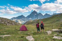 结合看发光的山峰庄严看法在日落高在阿尔卑斯 与野营的帐篷,焦点的背面图我 免版税图库摄影