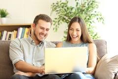 结合笑的观看在膝上型计算机的线内容 免版税库存照片