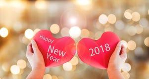 结合红色心脏与在金bokeh bac的文本新年好2018年 库存图片