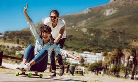 结合获得与滑板的乐趣在海滩 图库摄影