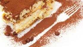 结块与叉子的图象的提拉米苏在板材洒与巧克力 免版税库存图片
