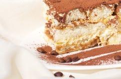 结块与叉子的图象的提拉米苏在板材洒与巧克力 库存图片