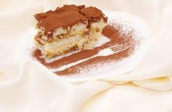 结块与叉子的图象的提拉米苏在板材洒与巧克力 免版税库存照片