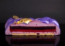 结块用在用食物金子装饰的镜子紫色釉的莓果奶油甜点,部分 库存照片