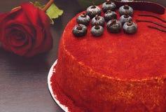 结块红色天鹅绒在桌在玫瑰旁边装饰用蓝莓莓果和巧克力 图库摄影